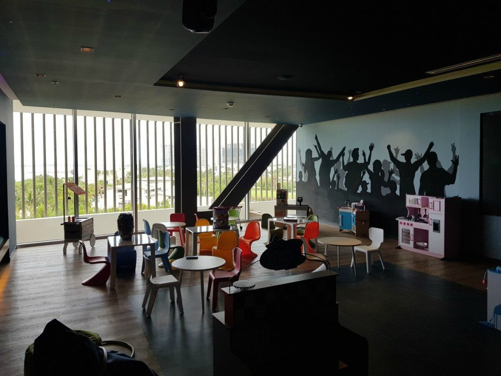 kids club interior with mini tables and chairs and a mural