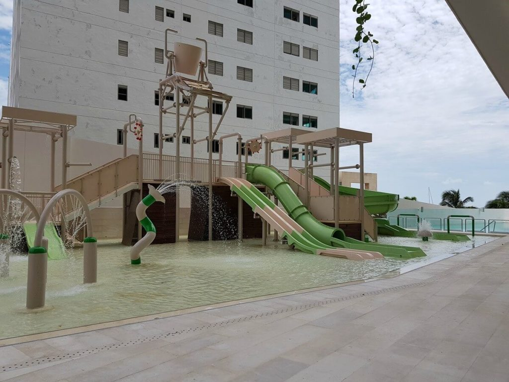 outdoor kids waterpark area with slides and sprinklers