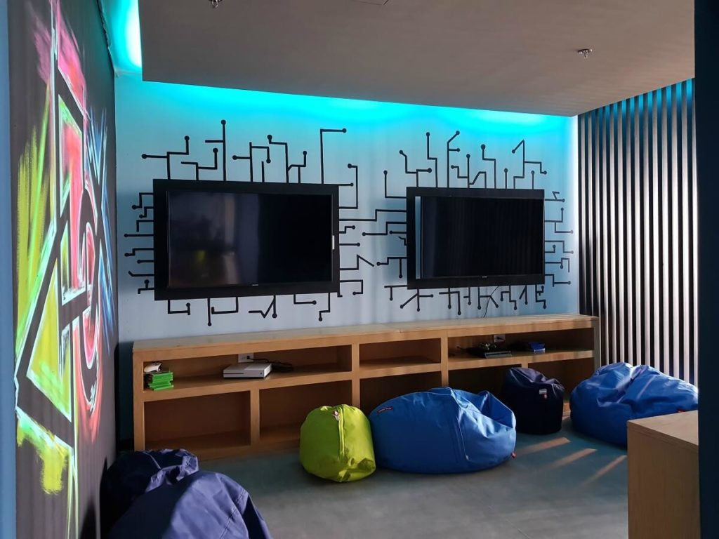colorful walls and video game consoles and bean bag chairs, teen club dreams vista cancun