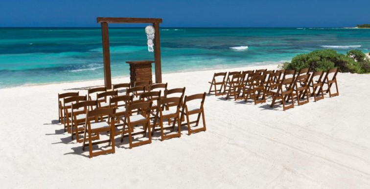 Unico Weddings on the beach - free ceremony set up with brown avant garde chairs and arch.