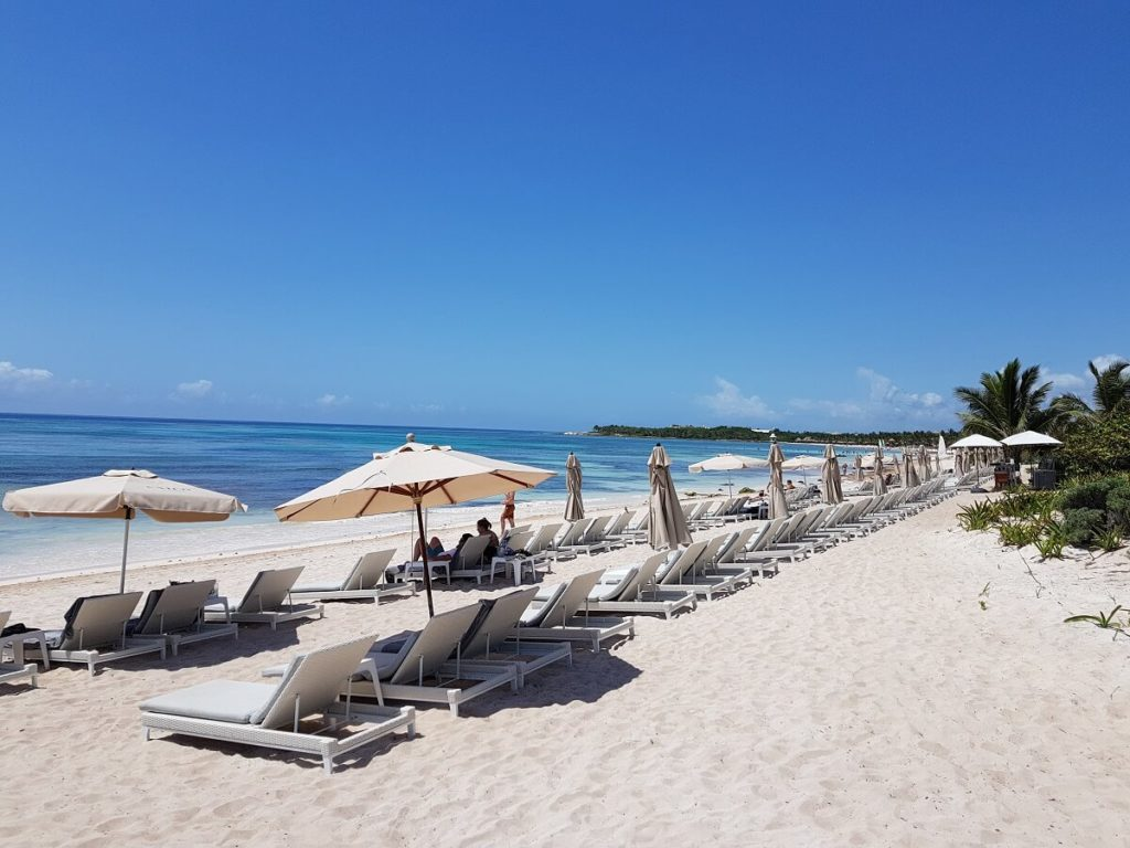 unico hotel beach area with white loungers, umbrellas and a calm ocean