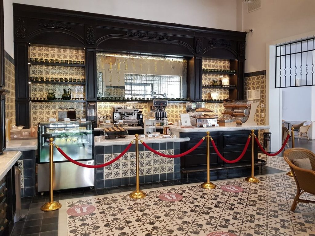 cafe area with artistic ceramic, dessert counter and coffee machines