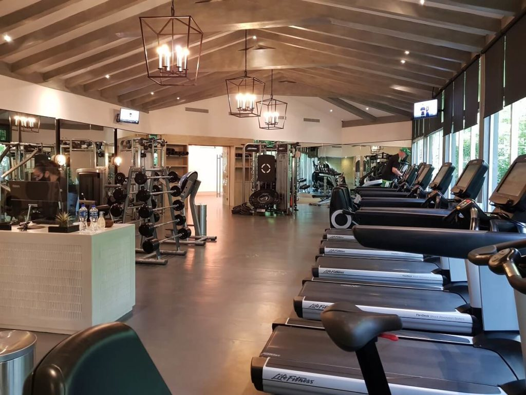 fitness center interior with treadmills and vaulted ceiling