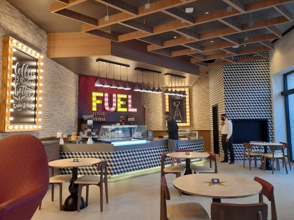 cafe interior with purple name fuel illuminated and dessert counter
