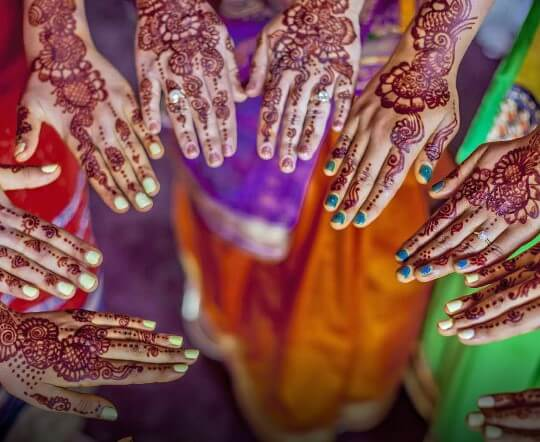 various hands with henna designs and a multi colored background
