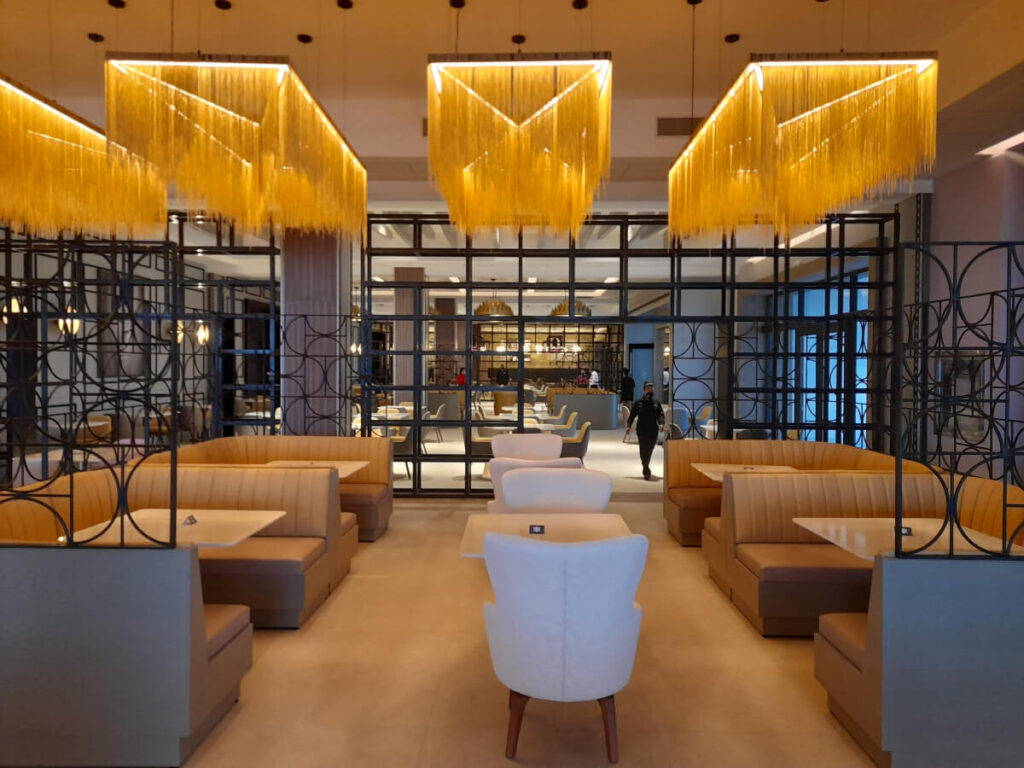 buffet restaurant interior with beige booths and modern champagne chandeliers