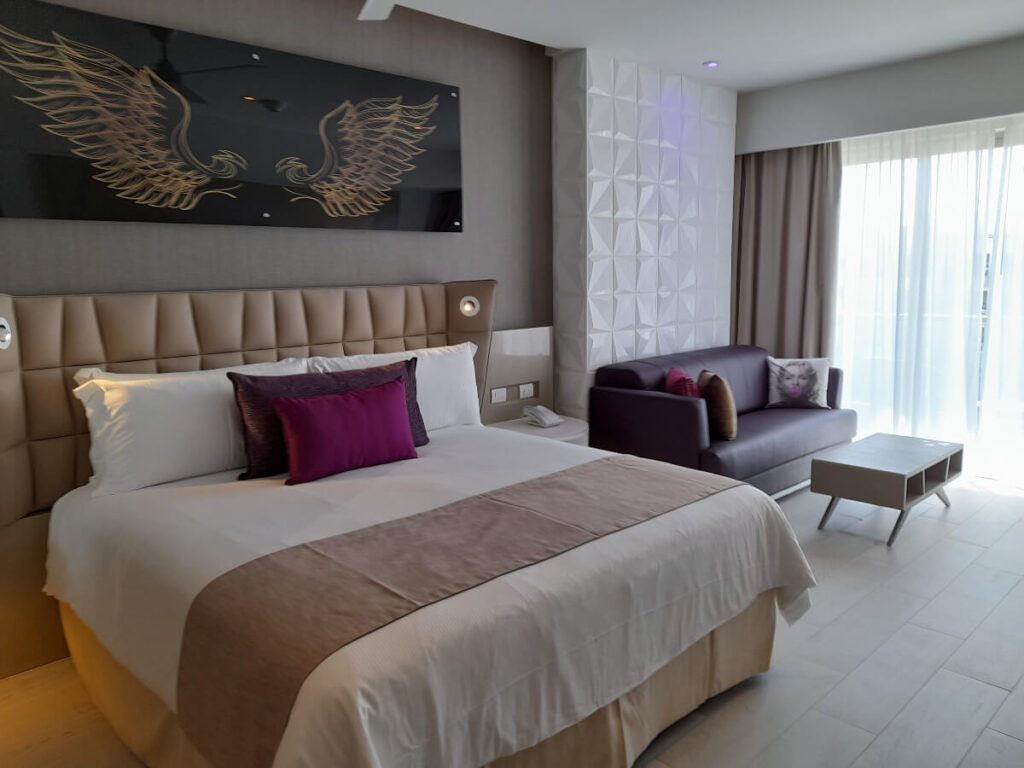 hotel room interior with king bed, sofa bed