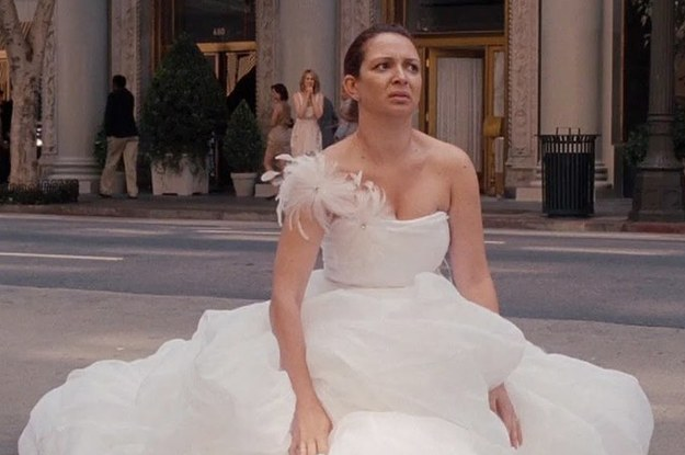 Bride in gown sitting on the street