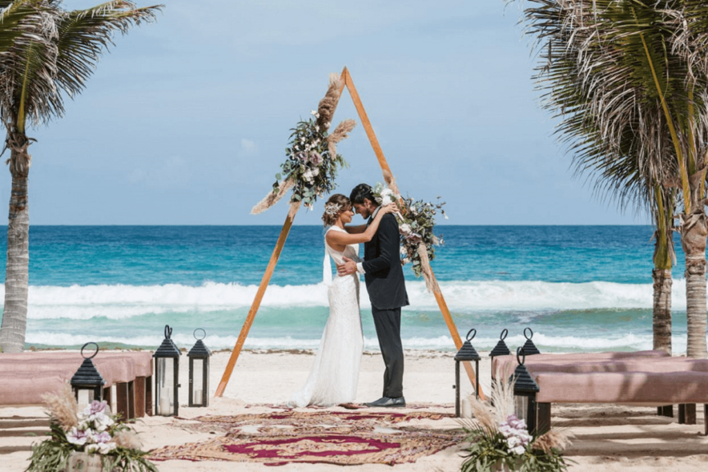 Couple getting married at Live Aqua Cancun under a flower arrangement with the sea behind them