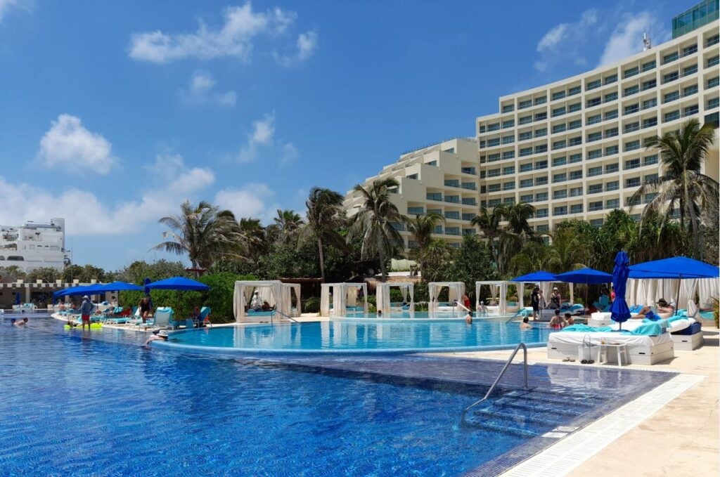 Pools and cabanas with blue umbrellas