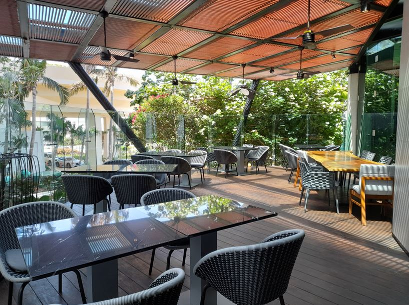 Restaurant with chairs in a deck and a big garden